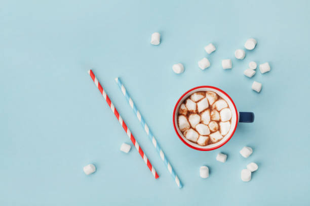 mug of hot cocoa or chocolate and straw on turquoise table top view. flat lay. - hot chocolate stock photos and pictures