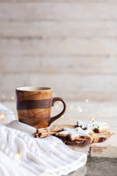 Mug of hot steamy tea, Christmas gingerbread cookies at wooden background with glares. stock photo