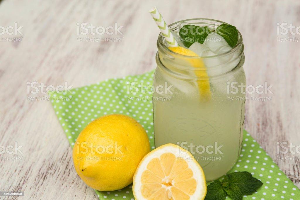 Mug of Lemonade and Lemons On White Wood Background stock photo