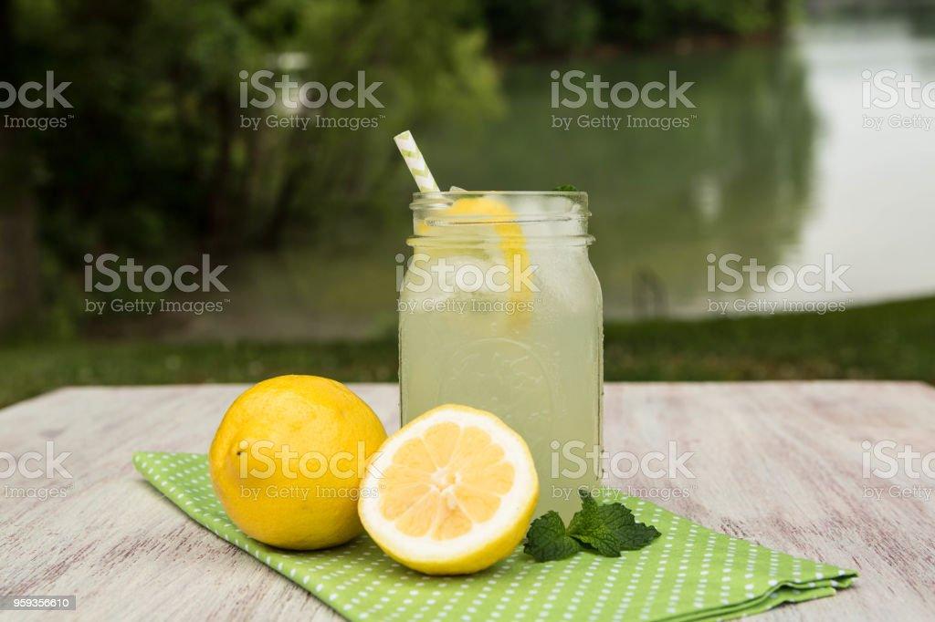 Mug of Lemonade With Lemons Outside By Lake stock photo