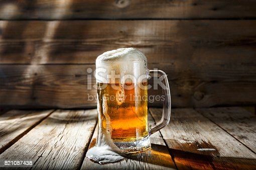 istock Mug of light beer with foam on a wooden table in a pub 821087438