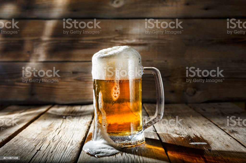 Mug of light beer with foam on a wooden table in a pub stock photo