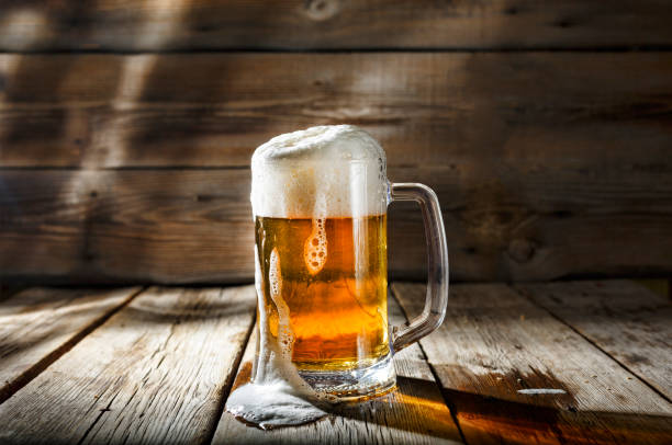 mug of light beer with foam on a wooden table in a pub - beer glass stock photos and pictures