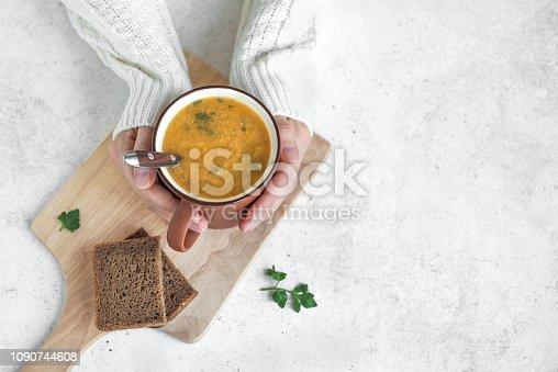 istock Mug of soup in hands 1090744608