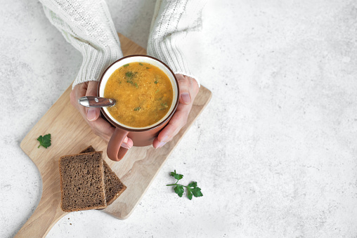 istock Mug of soup in hands 1090744608