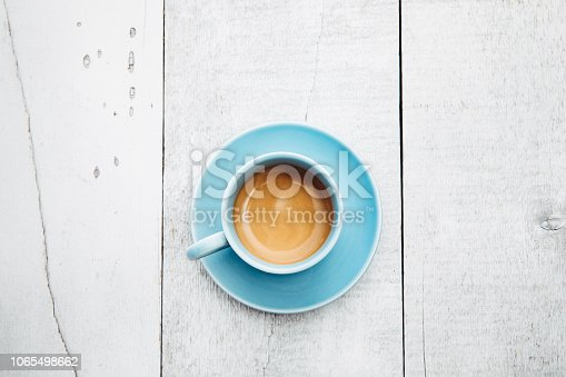 An overhead view of a freshly pulled shot of espresso, the crema still creamy and tan on top of the hot drink.  The baby blue mug sits on a whitewashed cedar wood table.