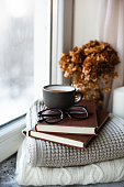 Cozy home with cup of coffee with glass and books. Hygge home interior