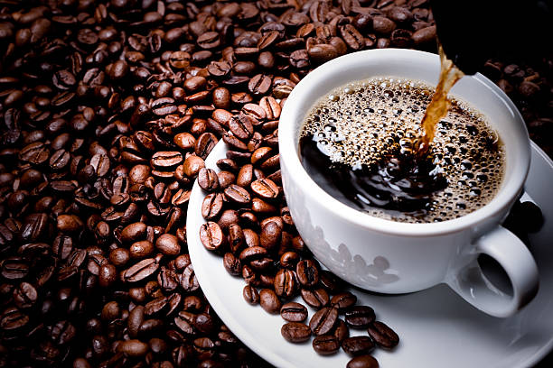 Mug on plate filled with coffee surrounded by coffee beans stock photo