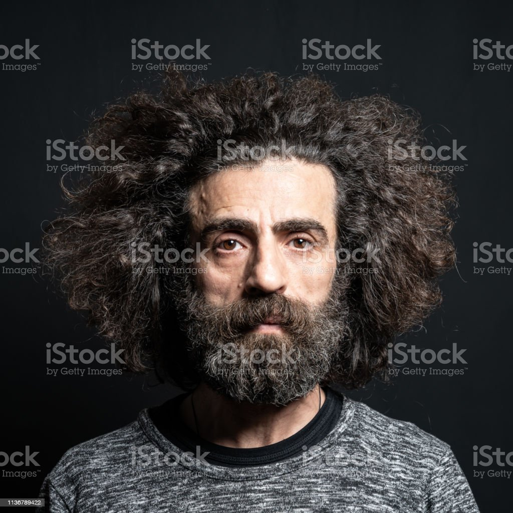 Portrait of mature adult man with long curly hair and beard. He is...