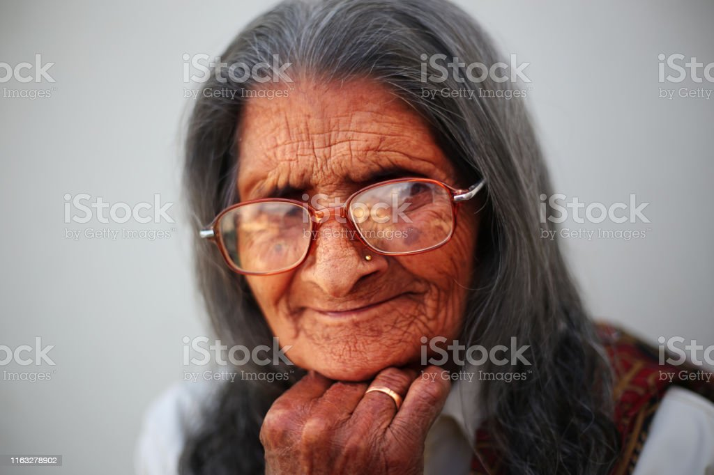 Old wrinkled women with eyeglasses close-up portrait against gray...