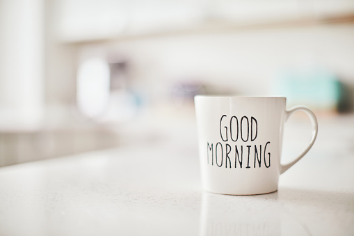 Mug with cheerful Good Morning message on kitchen counter