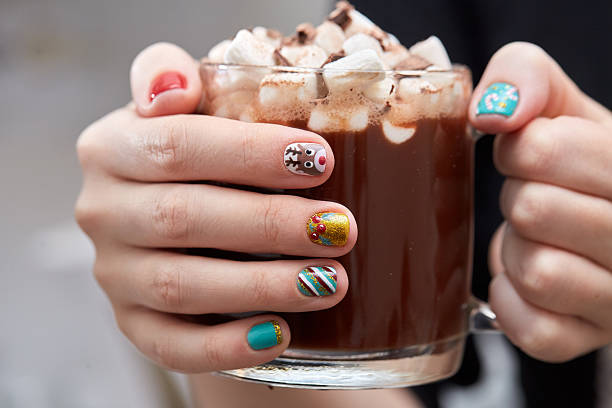 Mug with cocoa and marshmallows in female hands. stock photo