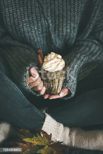 Woman in dark woolen sweater, grey jeans and white woolen socks sitting and holding mug with hot chocolate or coffee with whipped cream and cinnamon sticks in hands. Fall warming sweet drink