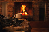 istock Mug with hot tea standing on a chair with woolen blanket in a cozy living room with fireplace. 1282305579