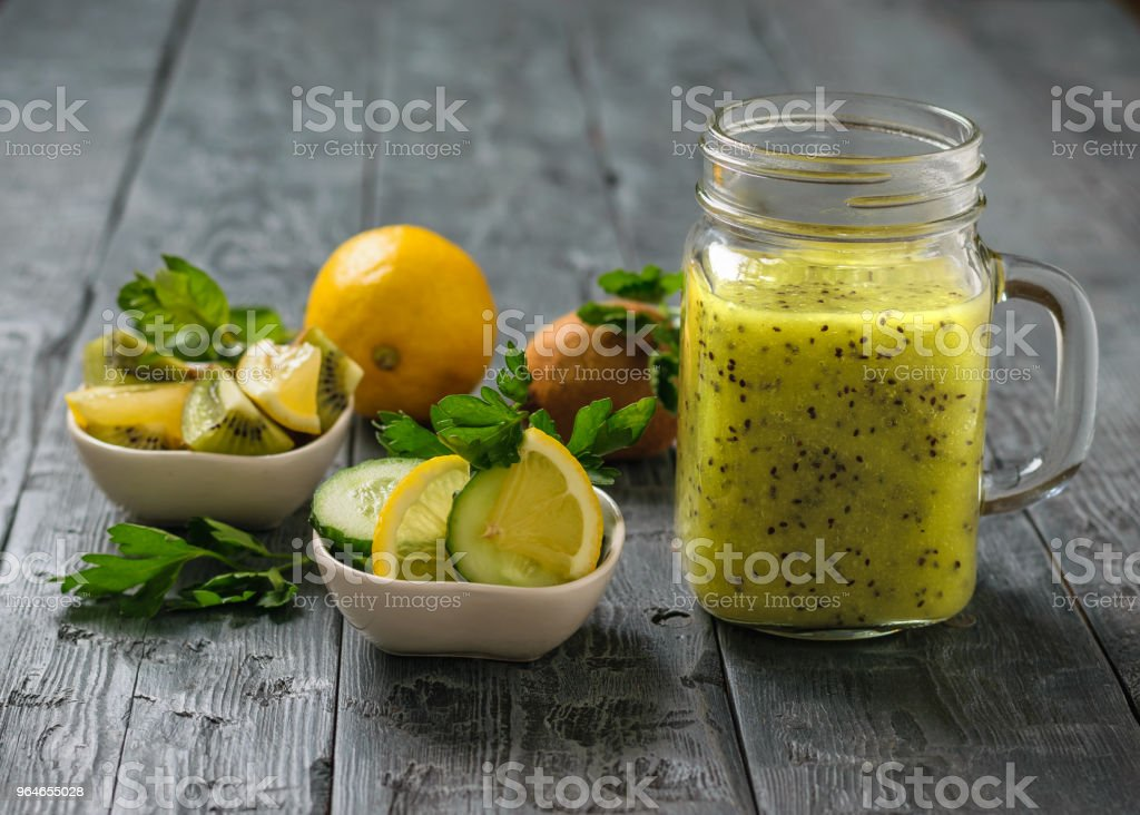 Mug with smoothies of kiwi, cucumber, lemon, parsley and mint on a rustic black table. royalty-free stock photo