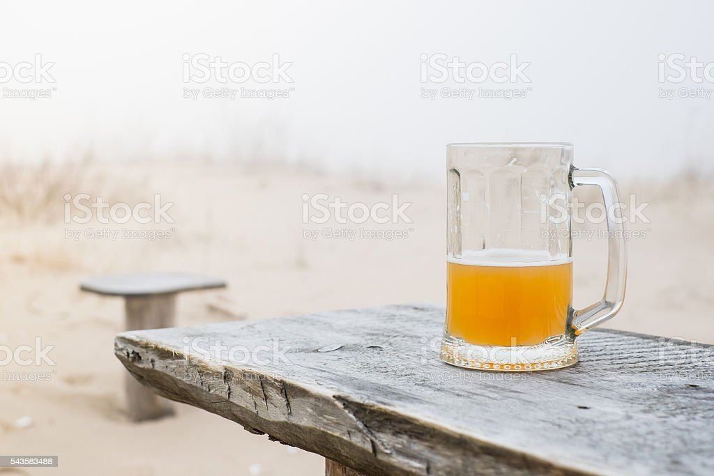 Mug with wheat beer on the bench stock photo