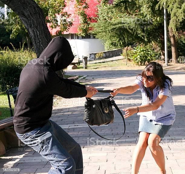 Mugger attacks to steal woman's shoulder bag.