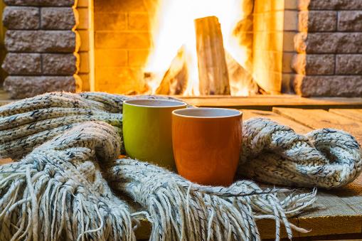 Mugs  for tea or coffee,  wool things near cozy fireplace.