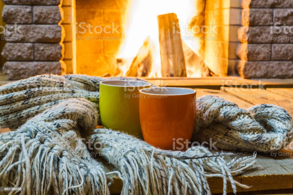 Mugs  for tea or coffee,  wool things near cozy fireplace. stock photo