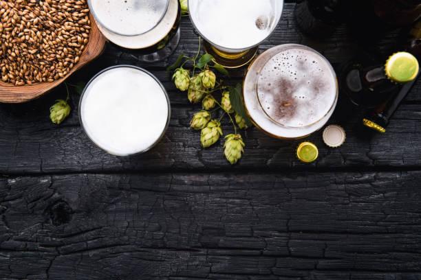 canecas de cerveja com lúpulo verde e trigo em fundo preto de madeira - ale - fotografias e filmes do acervo