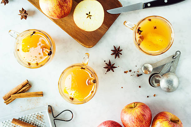 Mugs of Hot Spiced Mulled Apple Cider with Ingredients Three glass mugs of hot mulled apple cider heated with cinnamon sticks, star anise, and cloves on a marble countertop. Apples are on a wooden cutting board ready to be sliced and a grater is on the side for the spices. hot apple cider stock pictures, royalty-free photos & images
