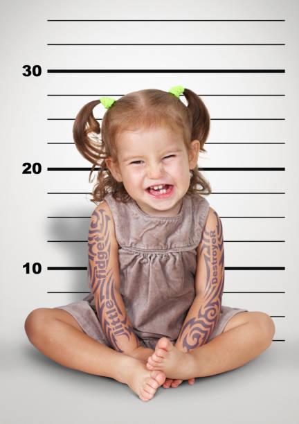 mugshot, lustige freche baby mit tattoo, ungehorsame kind konzept. - lausbub tattoo stock-fotos und bilder
