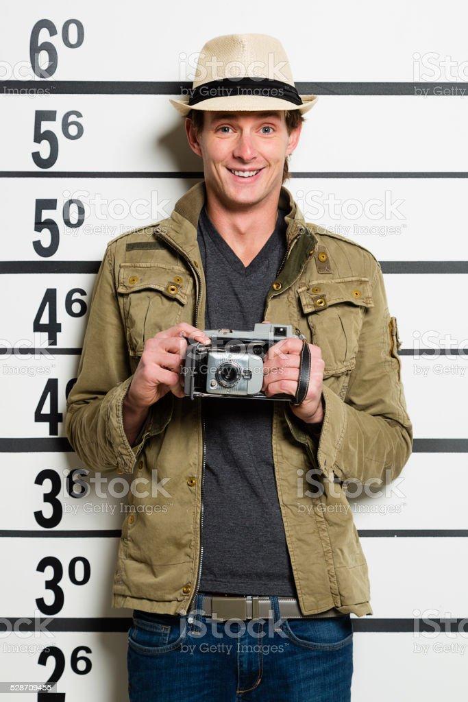 A mugshot/booking photo of a man holding a camera.