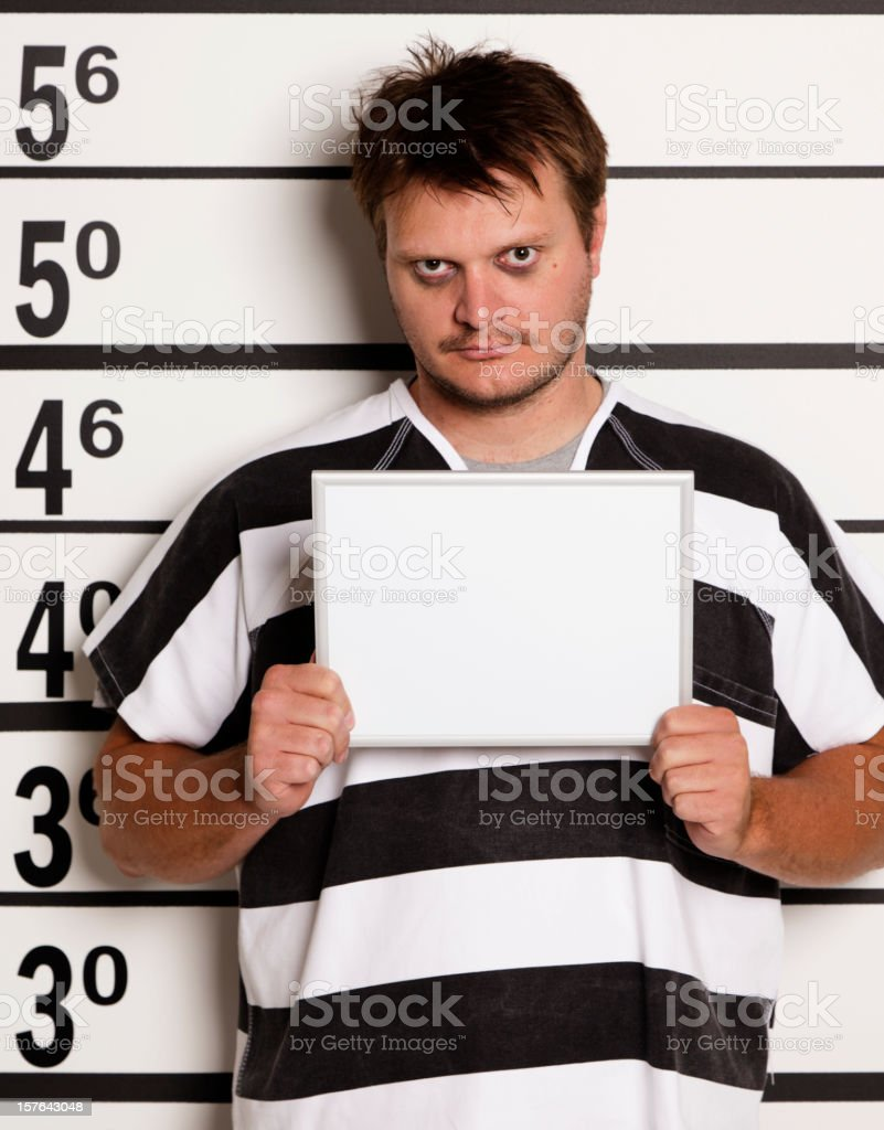 Mugshot of a Young Man in Prison Uniform stock photo