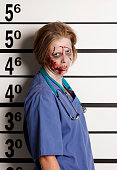 A mugshot/booking photo of a woman dressed as a zombie.