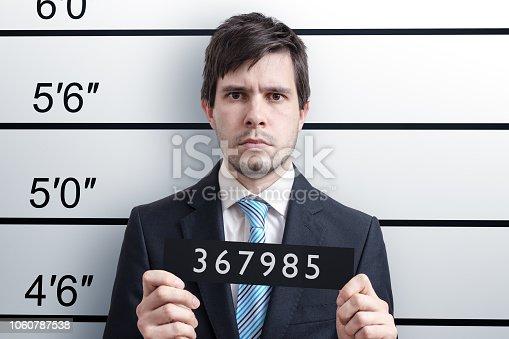Mugshot of young guilty man at police station.
