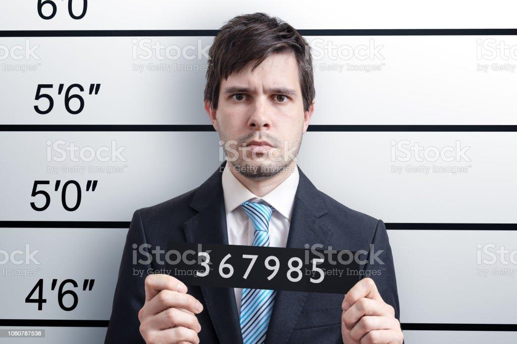 Mugshot of young guilty man at police station. stock photo