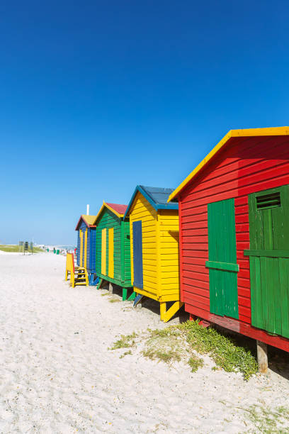 Muizenberg beach with white sand and colorful wooden cabins in Cape Town stock photo