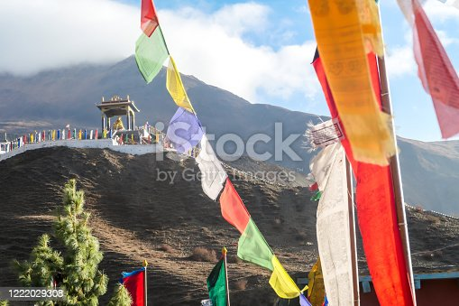 Prayer flags with a view on Buddhist temple located on a steep slope in Muktinath, Annapurna Circuit Trek in Nepal. The temple is richly ornated. In the back there is a Himalayan chain. Spirituality