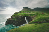 gasadalur village and mulafossur waterfall, faroe islands.