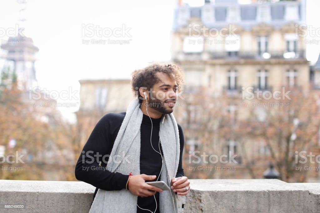Mulatto guy enjoying smartphone and earphones with Eiffel tower stock photo