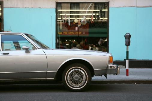 An old sedan car parked outside an Italian delicatessen in Little Italy, New York City, New York, USA.