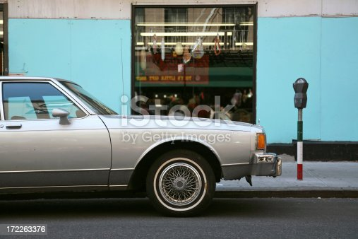 An old sedan car parked outside an Italian delicatessen in Little Italy, New York City, New York, USA.