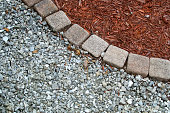 Looking down at square bricks form curve that separates mulch from gravel or small stones in backyard garden area with copy space.