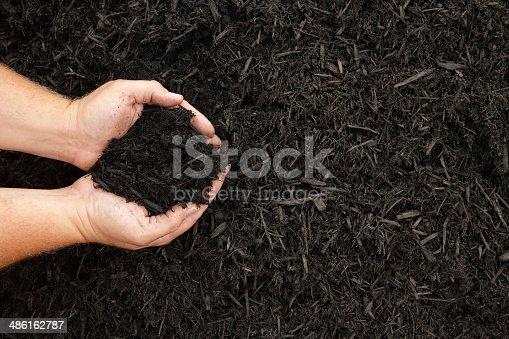 Hands displaying a handful of dark wood bark mulch