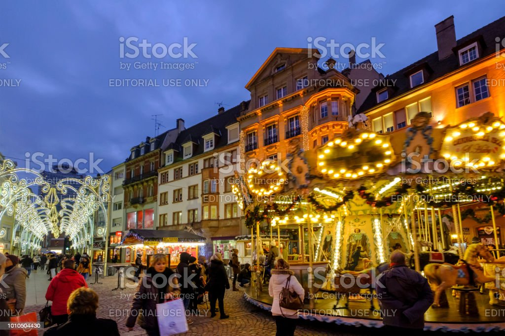 People enjoying the advent around the illuminated carousel in the old...
