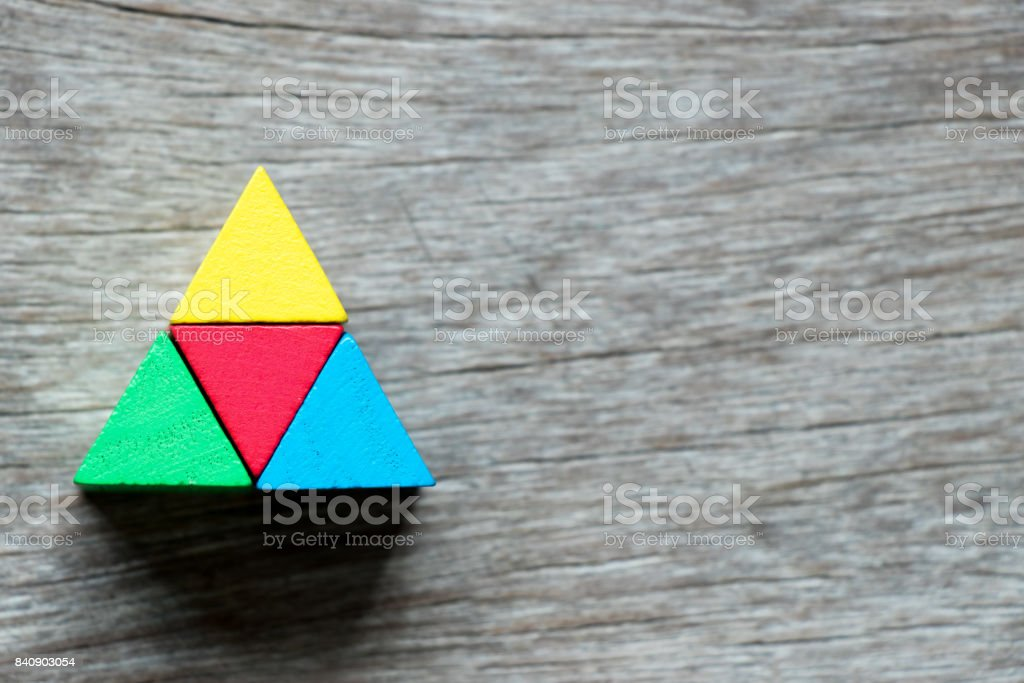 Mulit color toy block compound as triangle shape on wood background stock photo