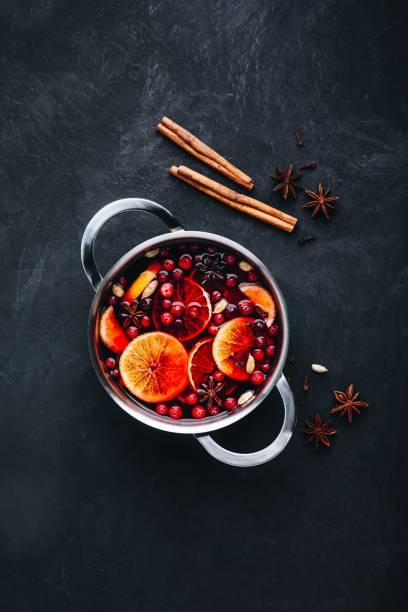 glühwein warme drank met cranberries, sinaasappelen, appels en specerijen op donkere betonnen achtergrond. - gluhwein stockfoto's en -beelden