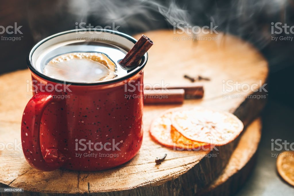 Mulled wine in a red ceramic mug over rustic wooden boards suppounded spices. royalty-free stock photo