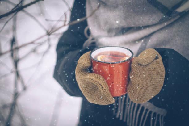 kadın el mittens kırmızı bir kaba mulled şarap. karlı kış orman sıcak kış içkide açık. kar taneleri ile noel arka plan - glühwein stok fotoğraflar ve resimler