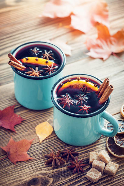 mulled wine in blue enameled rustic mugs with spices and citrus fruit on wooden table with autumn leaves. retro toned. - mulled wine stock photos and pictures