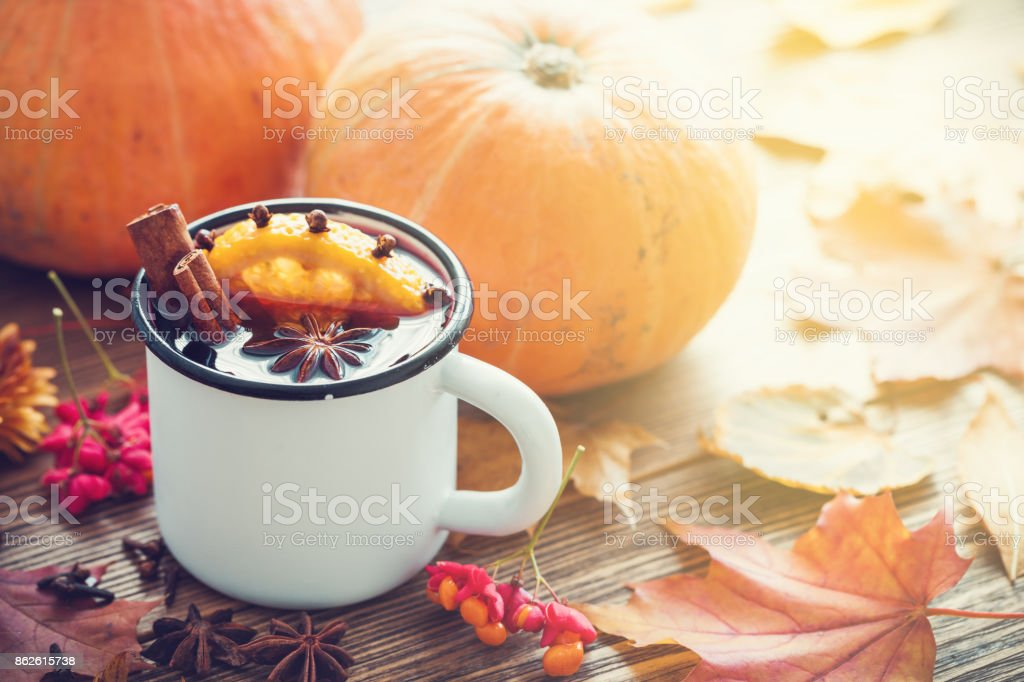 Mulled wine in enameled cup and pumpkins on wooden table with autumn leaves. stock photo