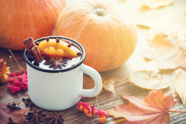 mulled wine in enameled cup and pumpkins on wooden table with autumn leaves. - gourd stock photos and pictures