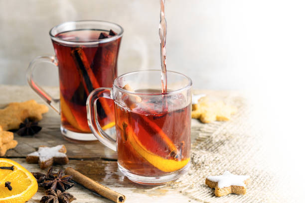 mulled wine in glass mugs with christmas cookies and spices like orange slices, cloves, star anise and cinnamon on a bright rustic table, background fades to white, copy space - mulled wine stock photos and pictures