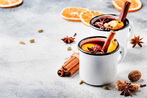 Mulled wine in white metal mugs with cinnamon, spices and orange on concrete background, traditional drink on winter holiday. Copy space for text