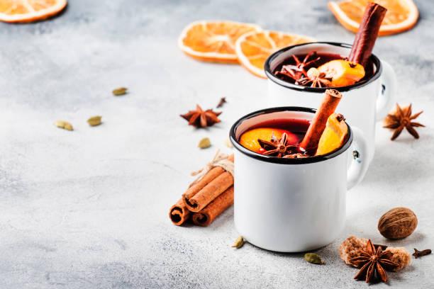 glühwein in witte metalen mokken met kaneel, specerijen en sinaasappel op betonnen achtergrond, traditionele drank op winter vakantie. ruimte kopiëren voor tekst - gluhwein stockfoto's en -beelden